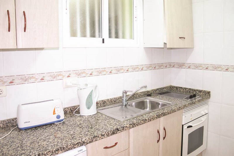 Playamar Apartments Levante Benidorm - Kitchen with oven, hob and fridge.